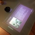 Durch das Verschieben von Büro-Utensilien kann man auf diesem Multi-Touch-Schreibtisch verschiedene Themenbereiche auswählen und vertiefen.