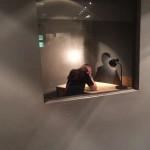 Blick aus der Ausstellung in den Verhörraum. Durch die Benutzung der Knochenschalllautsprecher im Tisch wird der/die Besucher/in in diese Haltung gebracht.