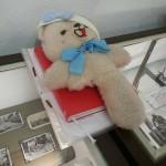 Der Teddy ohne Bein liegt auf der Vitrine zum Thema Minen.