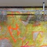Garderobe und Graffiti an der Bunkerwand schlagen eine Brücke durch alle Nutzungsphasen dieses Gebäudes.